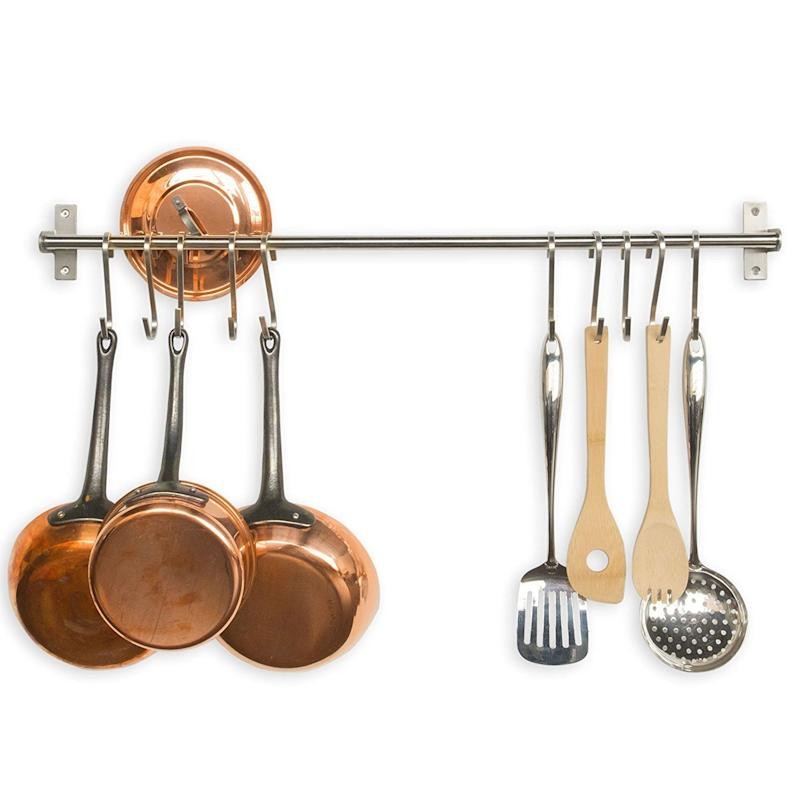 "Get your cookware out of valuable storage cabinets and onto unused wall space with <a href=""https://www.amazon.com/Fasthomegoods-Stainless-Steel-Gourmet-Kitchen/dp/B00X1N67QO/"" target=""_blank"">this kitchen rail with S hooks</a>."