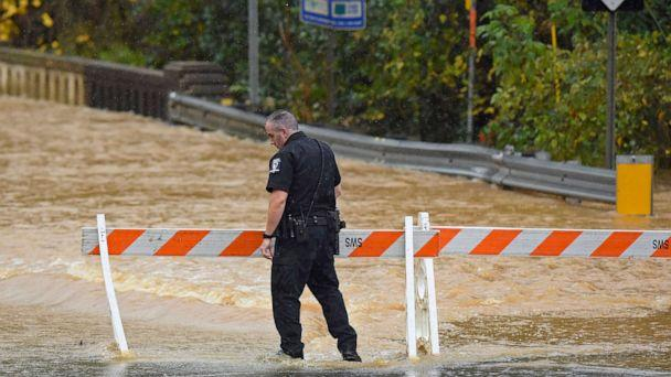 PHOTO: A Charlotte-Mecklenburg police officer blocks West Blvd. from local traffic as floodwater blocks the road in Charlotte, N.C., Thursday, Nov. 12, 2020. (Jeff Siner/The Charlotte Observer via AP)
