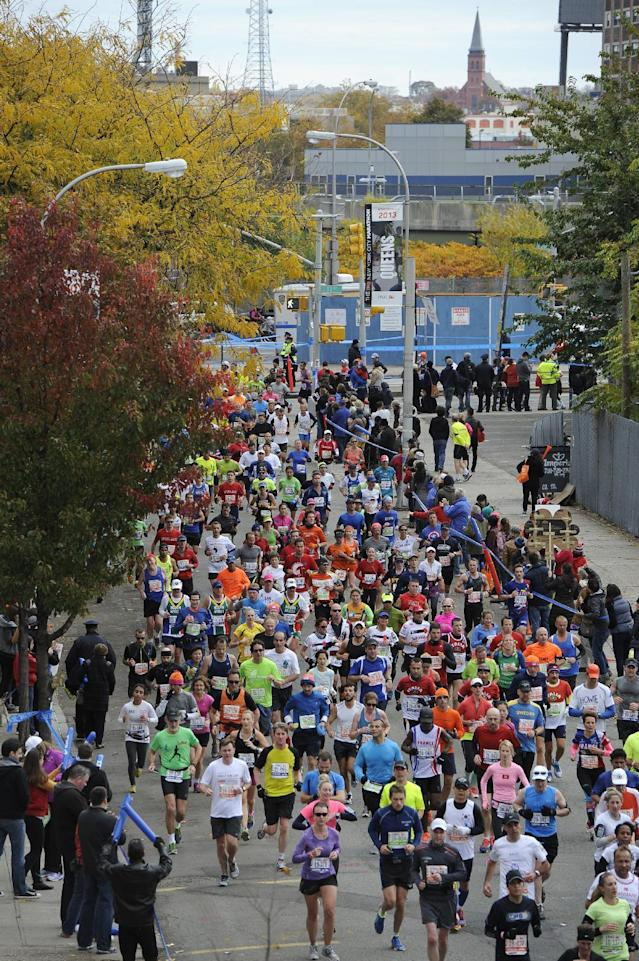 Runners race down 48th Ave in the Queens borough of New York during the New York City Marathon on Sunday, Nov. 3, 2013. New York. The New York City Marathon returned after a one-year absence with big crowds and heightened security. (AP Photo/Kathy Kmonicek)