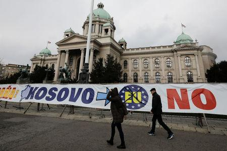 People walk past a banner in front of Serbian parliament building in central Belgrade