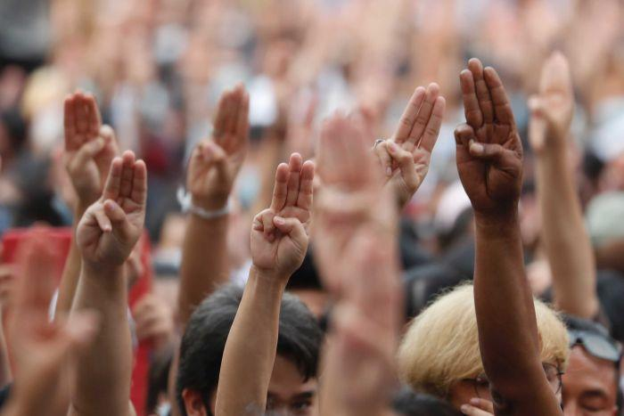 People raise their hands in the air with three fingers pointed in the sky.
