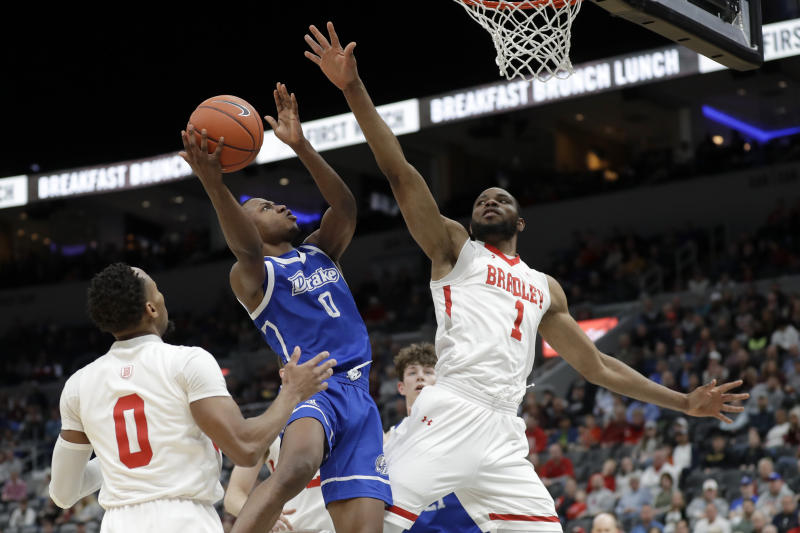 Drake's D.J. Wilkins shoots as Bradley's Danya Kingsby, left, and Ari Boya, right, defend during the second half of an NCAA college basketball game in the semifinal round of the Missouri Valley Conference men's tournament Saturday, March 7, 2020, in St. Louis. (AP Photo/Jeff Roberson)
