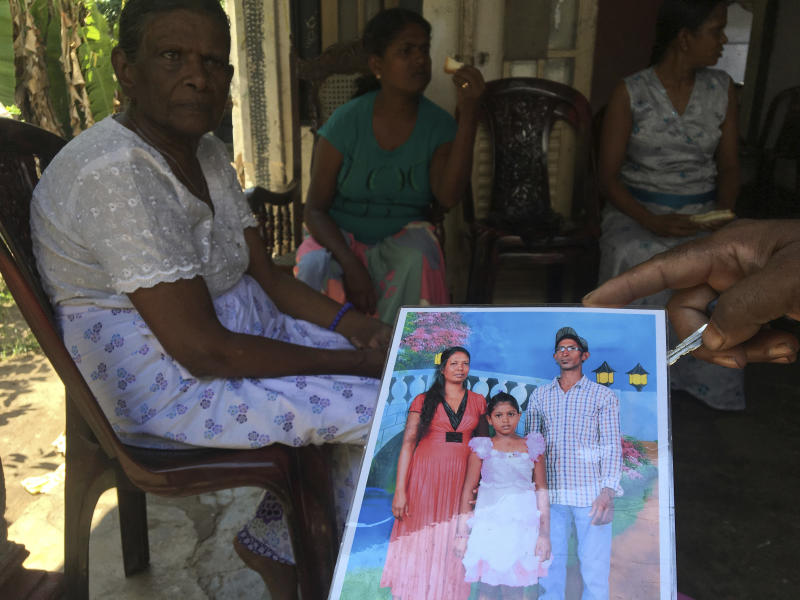 A family friend shows an image of Easter Sunday bomb blast victim Dileep Roshan, right in photo, who left behind a wife and daughter, in Negombo, Sri Lanka on Tuesday, April 23, 2019. (AP Photo/Rishabh Jain)
