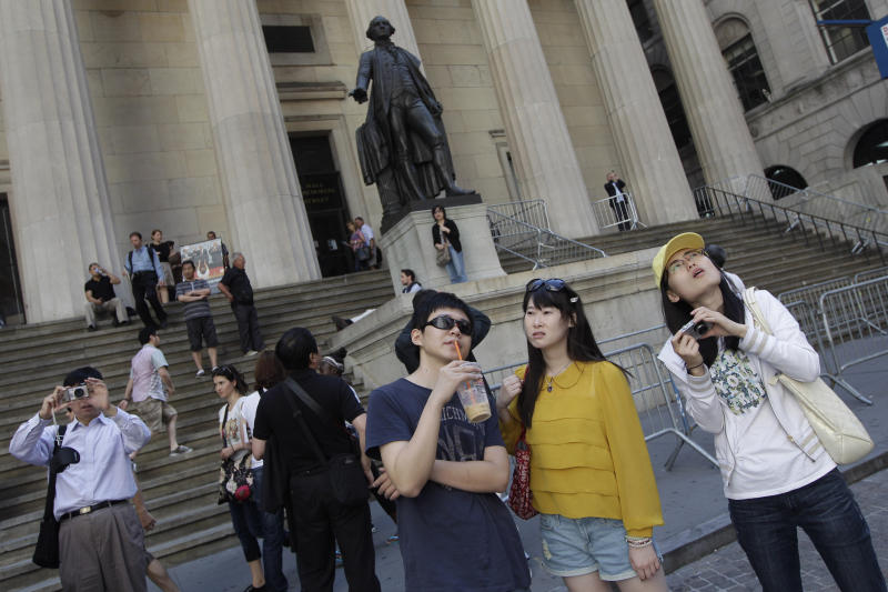 FILE - In this June 15, 2012, file photo, a group of tourists from China take in the sights of the New York Stock Exchange and Federal Hall National Memorial, in New York. With tens of millions of Chinese ordered to stay put and many others opting to avoid travel as the new coronavirus spreads, tourism around the global is taking a heavy hit during one of the biggest travel seasons, the Lunar New Year. (AP Photo/Mary Altaffer, File)