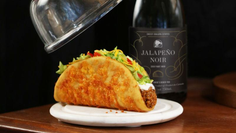 Taco Bell Chalupa on white plate atop wooden table with bottle of Taco Bell Jalapeno Noir on the side