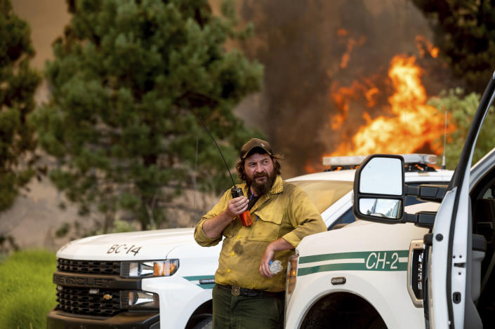 U.S. Forest Service firefighter Chris Voelker monitors the Sugar Fire, part of the Beckwourth Complex Fire, burning in Plumas National Forest, Calif., on Friday, July 9, 2021. The Beckwourth Complex — a merging of two lightning-caused fires — headed into Saturday showing no sign of slowing its rush northeast from the Sierra Nevada forest region after doubling in size only a few days earlier. (AP Photo/Noah Berger)