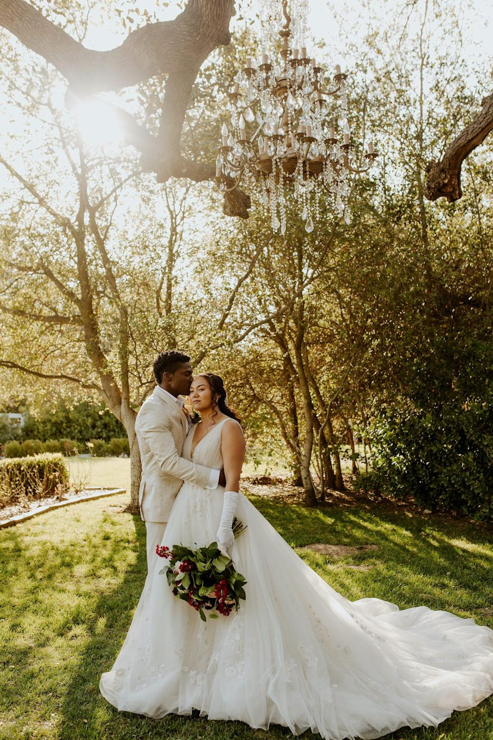 A bride and groom embrace in a field surrounded by trees.