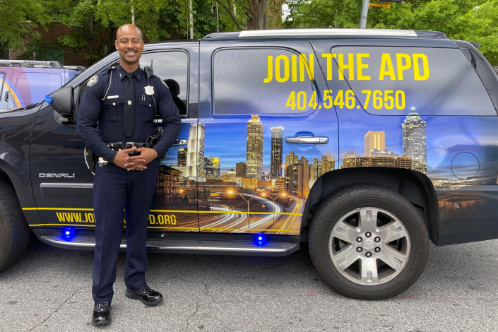 """In this May 5, 2021, photo Atlanta Police Officer Philip Darrett poses for a photo in front of the SUV he uses to help recruit new officers, in Atlanta. Darrett has been tapped to serve as """"Your Favorite Recruiter,"""" appearing in videos that are streamed live on social media. He pops up at locations around Atlanta urging people to come out and chat with him about policing. (AP Photo/Kate Brumback)"""