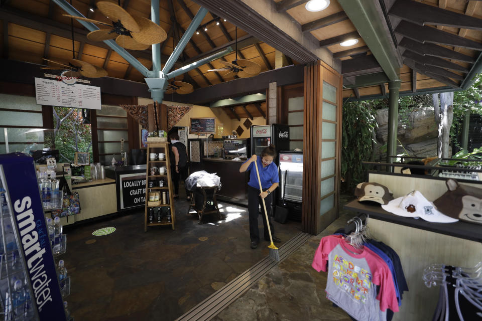 Workers clean a souvenir shop before the reopening of the San Diego Zoo, Thursday, June 11, 2020, in San Diego. California's tourism industry is gearing back up with the state giving counties the green light to allow hotels, zoos, aquariums, wine tasting rooms and museums to reopen Friday. (AP Photo/Gregory Bull)