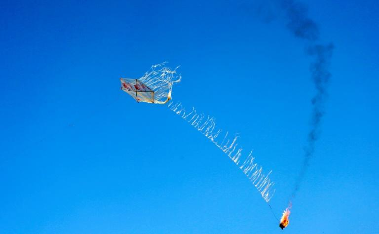 A kite carrying a Molotov cocktail is flown by Palestinian youths over the Gaza-Israel border on April 18, 2018