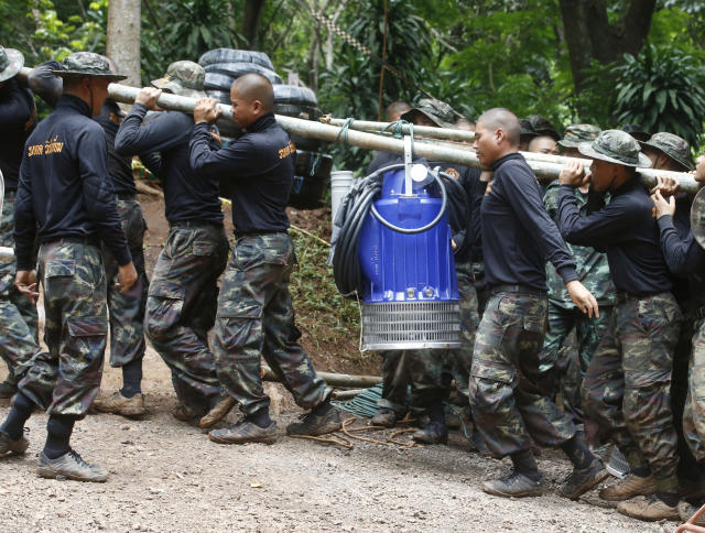 <p>Soldiers carry a pump to help drain the rising floodwater in a cave where 12 boys and their soccer coach had been trapped since June 23, in Mae Sai, Chiang Rai Province, in northern Thailand, Friday, July 6, 2018. (Photo: Sakchai Lalit/AP) </p>