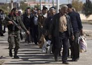 """FILE -- In this Tuesday, October 29, 2013 file photo, a Syrian soldier escorts men as they arrive from the rebel-held suburb of Moadamiyeh to government-held territory, in Damascus, Syria. In one besieged neighborhood after another, weary rebels have turned over their weapons to the Syrian government in exchange for an easing of suffocating blockades that have prevented food, medicine and other staples from reaching civilians trapped inside. The government touts the truces as part of its program of """"national reconciliation"""" to end Syria's crisis, which has killed more than 140,000 people since March 2011. (AP Photo/Dusan Vranic, File)"""