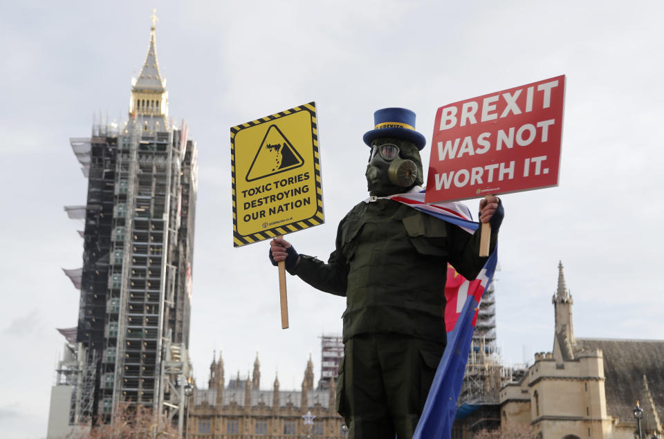 A pro EU protestor stands in parliament square in front of Parliament during the debate in the House of Commons on the EU (Future Relationship) Bill in London, Wednesday, Dec. 30, 2020.The European Union's top officials have formally signed the post-Brexit trade deal with the United Kingdom, as lawmakers in London get set to vote on the agreement. (AP Photo/Frank Augstein)