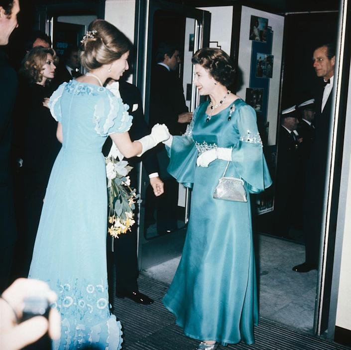<p>For the premiere of <em>Murder on the Orient Express</em>, Queen Elizabeth added diamond and sapphire jewelry to an elegant teal chiffon evening gown with bell sleeves and crystal embroidery. Her Majesty accessorized the look with white elbow-length gloves and a silver beaded clutch.</p>