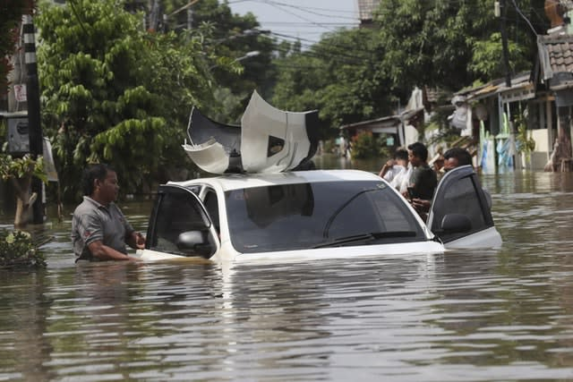 A resident inspects a car in a flooded neighbourhood in Tanggerang outside Jakarta, Indonesia