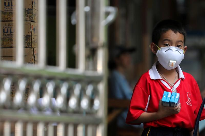 FILE PHOTO: Student wears anti-particle mask as he waits to be picked up at school in Bangkok