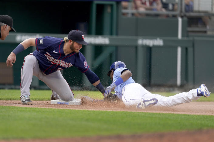 Kansas City Royals' Jarrod Dyson beats the tag by Minnesota Twins third baseman Josh Donaldson to advance to third on a ground out hit into by Jorge Soler during the ninth inning of a baseball game Saturday, June 5, 2021, in Kansas City, Mo. The Twins won 5-4. (AP Photo/Charlie Riedel)