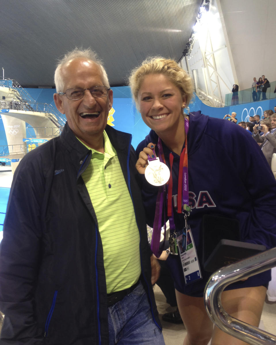 In this July 2012 photo provided by Joan Beisel, Olympic medalist swimmer Elizabeth Beisel, right, stands for a photo with her father Ted Beisel, left, at the 2012 Olympics, in London. Beisel competed in three Olympics, but she's never taken on a challenge quite like this. She will attempt to become the first woman to swim from the Rhode Island mainland to Block Island. The 10.4-mile swim is to honor her father, who died July 1 after being diagnosed with pancreatic cancer. Beisel has raised more than $121,000 for the fight against cancer and knows that she brought some meaning to her father's life in his final months. (Joan Beisel via AP)