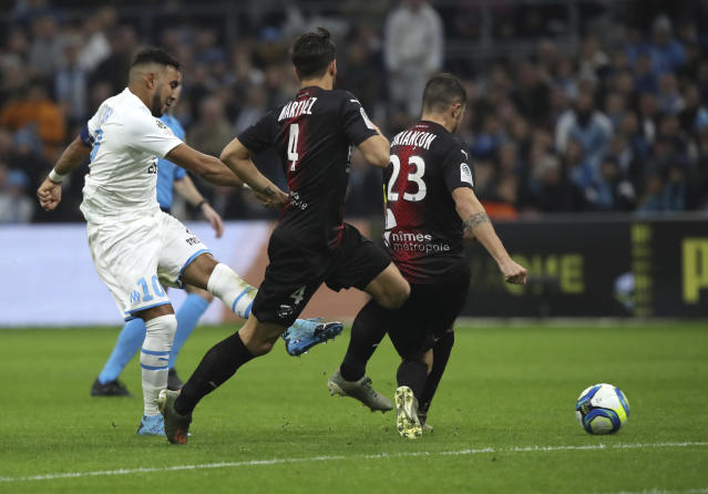 Marseille's Dimitri Payet, left, makes an attempt to score during the French League One soccer match between Marseille and Nimes at the Velodrome stadium in Marseille, southern France, Saturday, Dec. 21, 2019. (AP Photo/Daniel Cole)