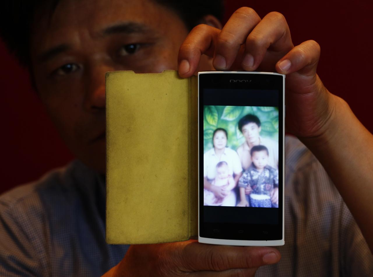 """Liu Kun, whose younger brother Liu Qiang was onboard Malaysia Airlines Flight MH370 which disappeared on March 8, shows a picture of his brother (top R) on his mobile phone during an interview with Reuters in Beijing July 18, 2014. World leaders demanded an international investigation into Thursday's shooting down of Malaysia Airlines Flight MH17 with 298 people on board over eastern Ukraine in a tragedy that could mark a pivotal moment in the worst crisis between Russia and the West since the Cold War. The loss of MH17 is the second devastating blow for Malaysia Airlines this year, following the mysterious disappearance of Flight MH370 in March, which vanished with 239 passengers and crew on board on its way from Kuala Lumpur to Beijing. Liu Kun said he is """"empathetic to family members of passengers aboard MH17"""". REUTERS/Kim Kyung-Hoon (CHINA - Tags: DISASTER TRANSPORT POLITICS)"""