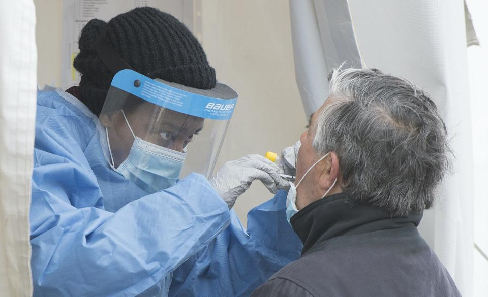 A health-care worker swabs a man at a walk-in COVID-19 test clinic.