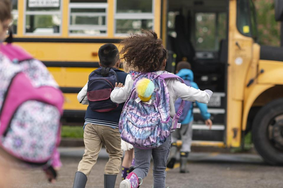 Diverse group of happy children getting on school bus