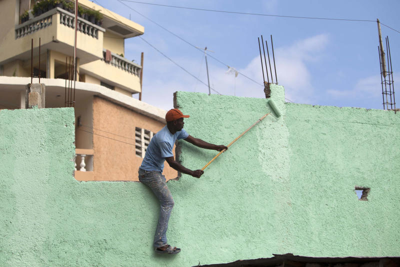 "In this March 21, 2013 photo, a man paints green the exterior wall of a home in Jalousie, a cinder block shantytown in Petionville, Haiti. The $1.4 million effort titled ""Beauty versus Poverty: Jalousie in Colors"" is part of a government project to relocate people from the displacement camps that sprouted up after Haiti's 2010 earthquake. (AP Photo/Dieu Nalio Chery)"