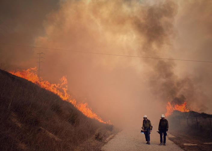 This Tuesday Oct. 12, 2021, photo provided by Santa Barbara County Fire, Santa Barbara County Fire Hand Crew members fight fire with fire and burn off pockets of grass along northbound Highway 101 north of Arroyo Hondo Canyon in Santa Barbara County, Calif. / Credit: Mike Eliason / AP