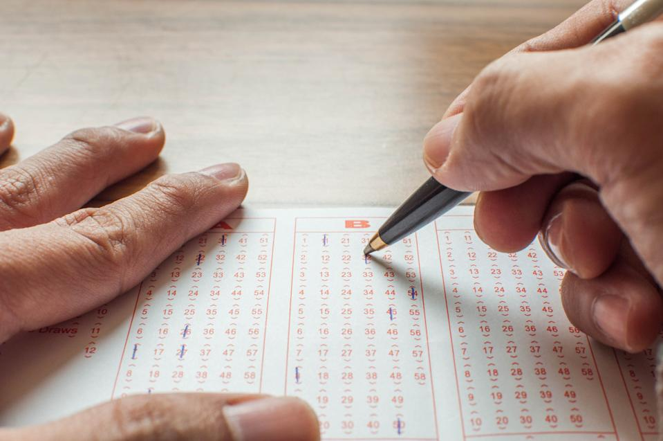 Close up of hands filling up a lottery ticket form a concept of gambling