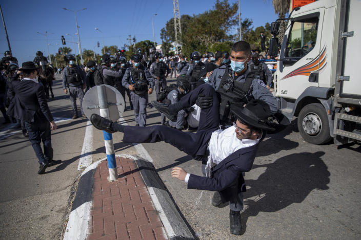 File - In this Sunday, Jan. 24, 2021 file photo, Israeli police officers clash with ultra-Orthodox Jews in Ashdod, Israel,. Ultra-Orthodox demonstrators clashed with Israeli police officers dispatched to close schools in Jerusalem and Ashdod that had opened in violation of coronavirus lockdown rules, on Sunday. (AP Photo/Oded Balilty, File)
