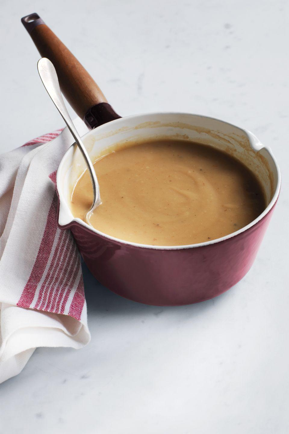 """<p>This star-worthy gravy is made by simmering turkey wing drippings with chicken broth, chopped carrot and onions, and dried thyme. Serve half the batch with dinner and save the rest — it can be stored in the freezer for up to one month.</p><p><a href=""""https://www.womansday.com/food-recipes/food-drinks/recipes/a10860/make-ahead-turkey-gravy-recipe-122223/"""" rel=""""nofollow noopener"""" target=""""_blank"""" data-ylk=""""slk:Get the Make-Ahead Turkey Gravy recipe."""" class=""""link rapid-noclick-resp""""><em><strong>Get the Make-Ahead Turkey Gravy recipe.</strong></em></a></p>"""