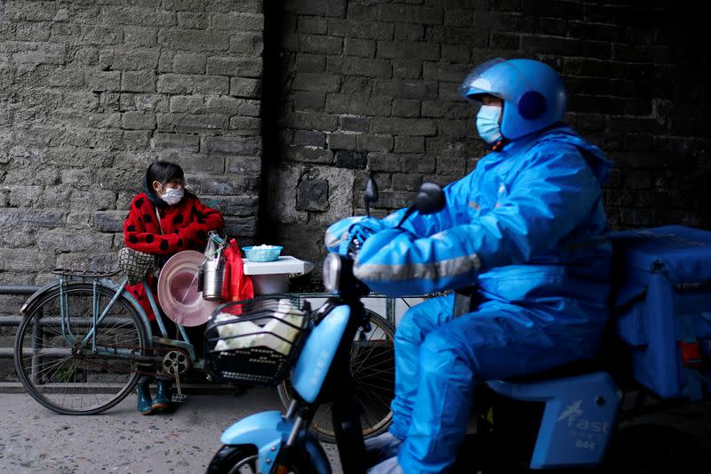 Delivery worker rides a vehicle past a vendor waiting for customers in Jingzhou