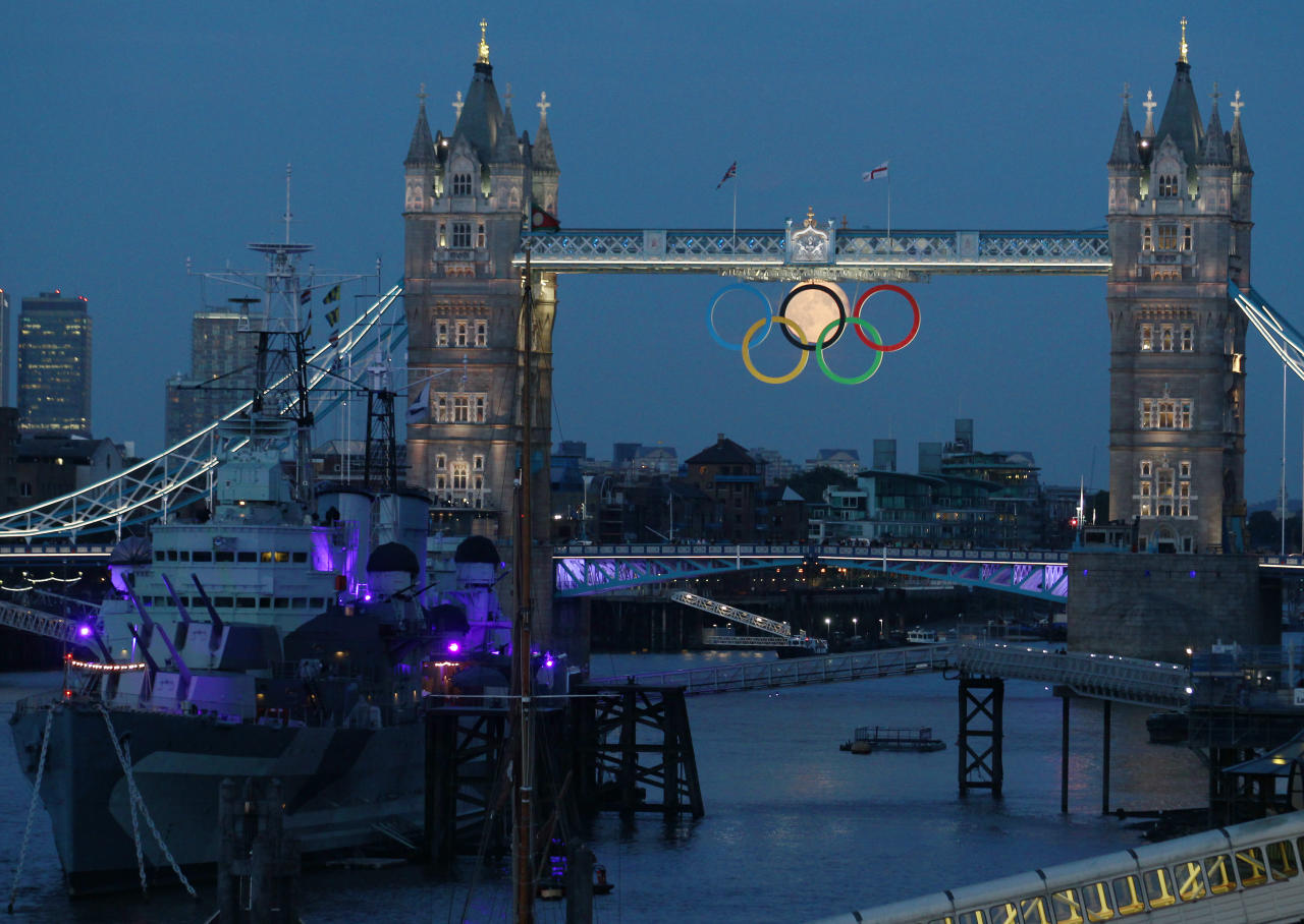 The full moon rises through the Olympic Rings hanging beneath Tower Bridge, near the HMS Belfast museum warship, during the London 2012 Olympic Games August 3, 2012.  REUTERS/Luke MacGregor  (BRITAIN - Tags: SPORT OLYMPICS ENVIRONMENT CITYSPACE)