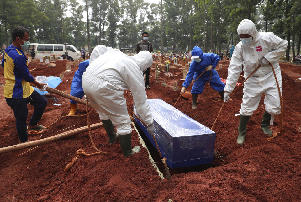 Workers in protective gear lower a coffin of a COVID-19 victim to a grave for burial at the Cipenjo Cemetery in Bogor, West Java, Indonesia, Wednesday, July 14, 2021. The world's fourth most populous country has been hit hard by an explosion of COVID-19 cases that have strained hospitals on the main island of Java. (AP Photo/Achmad Ibrahim)