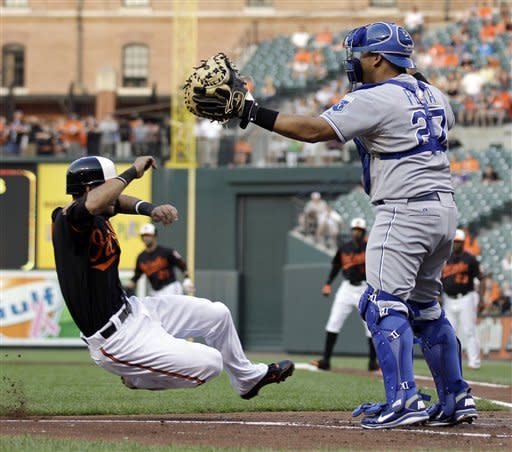 Baltimore Orioles' Robert Andino, left, slides into home plate for a run on a sacrifice fly by Adam Jones as Kansas City Royals catcher Brayan Pena waits for a throw in the first inning of a baseball game in Baltimore, Friday, May 25, 2012. (AP Photo/Patrick Semansky)