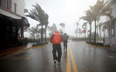 People walk along a street in South Beach as Hurricane Irma arrives at south Florida, in Miami Beach, Florida - Credit: CARLOS BARRIA