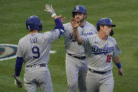 Los Angeles Dodgers' Gavin Lux (9) high-fives Max Muncy (13) and Will Smith (16) after they scored off of a line drive hit by Matt Beaty during the fourth inning of a baseball game against the Los Angeles Angels Saturday, May 8, 2021, in Anaheim, Calif. (AP Photo/Ashley Landis)