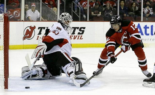 New Jersey Devils ring wing Damien Brunner (12), of the Czech Republic, scores a goal on Ottawa Senators goalie Robin Lehner (40), of Sweden, during the second period of an NHL hockey game, Wednesday, Dec. 18, 2013, in Newark, N.J. (AP Photo/Julio Cortez)
