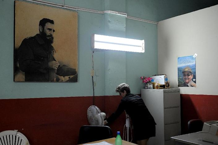 A woman works next to poster of Cuban late president Fidel Castro and Cuban president Raul Castro at her office in Havana, on February 23, 2017 (AFP Photo/YAMIL LAGE)