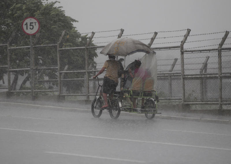 A Filipino man pedals his pedicab during a brief rainfall at Navotas, north of Manila, Philippines on Monday, Aug. 12, 2013. Powerful Typhoon Utor battered the northern Philippines on Monday, toppling power lines and dumping heavy rains across mountains, cities and food-growing plain. The storm killed at least one man in a landslide and left 45 fishermen missing. (AP Photo/Aaron Favila)