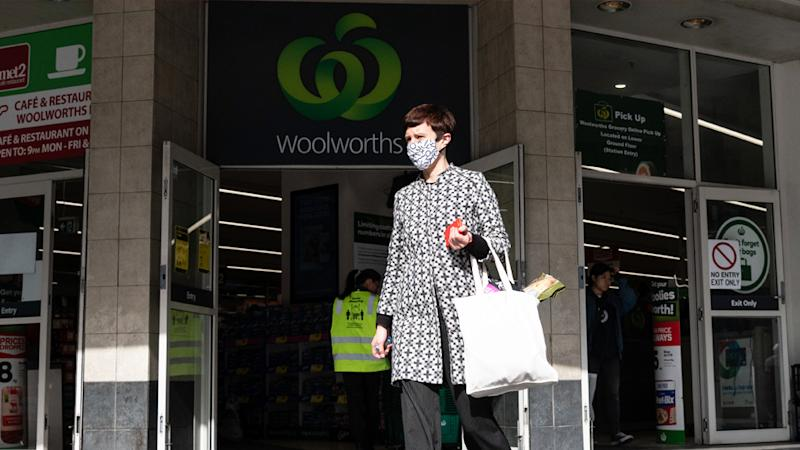 A woman is seen leaving a Woolworths store while wearing a mask