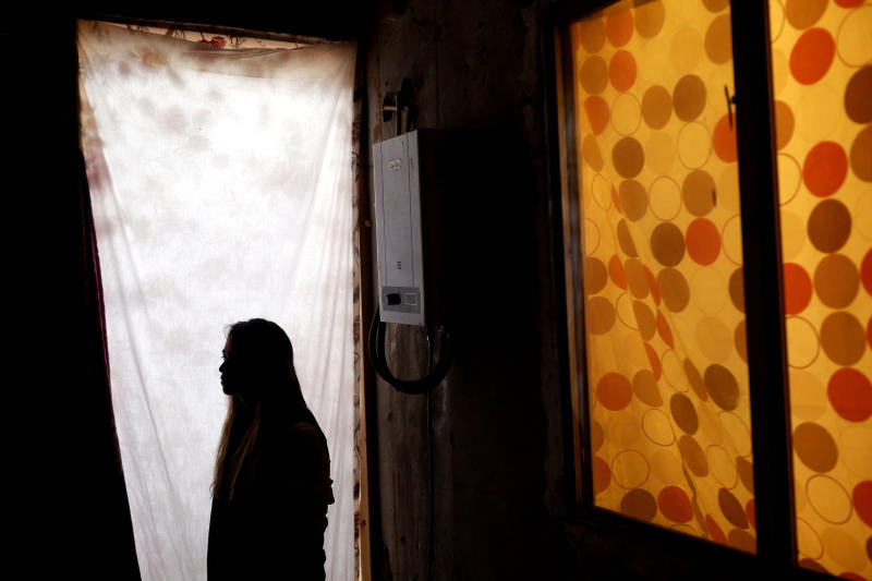 """In this Tuesday, Nov. 5, 2019, photo, Lizbeth poses for a portrait in a relative's home in Tijuana, Mexico. Lizbeth, a Salvadoran woman seeking asylum in the United States, never thought she would be returned to Mexico to wait for the outcome of her case, after suffering multiple assaults, and being kidnapped into prostitution on her journey through Mexico. Critics of the Trump administration's """"Migrant Protection Protocols"""" policy, say it denies asylum seekers fair and humane treatment, largely by forcing them to wait in a country plagued by large pockets of drug-fueled violence, demonstrated this week by the slaughter near the U.S. border of several children and women. (AP Photo/Gregory Bull)"""