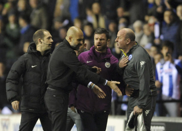 Manchester City manager Josep Guardiola, second from left, argues with Wigan manager Paul Cook,