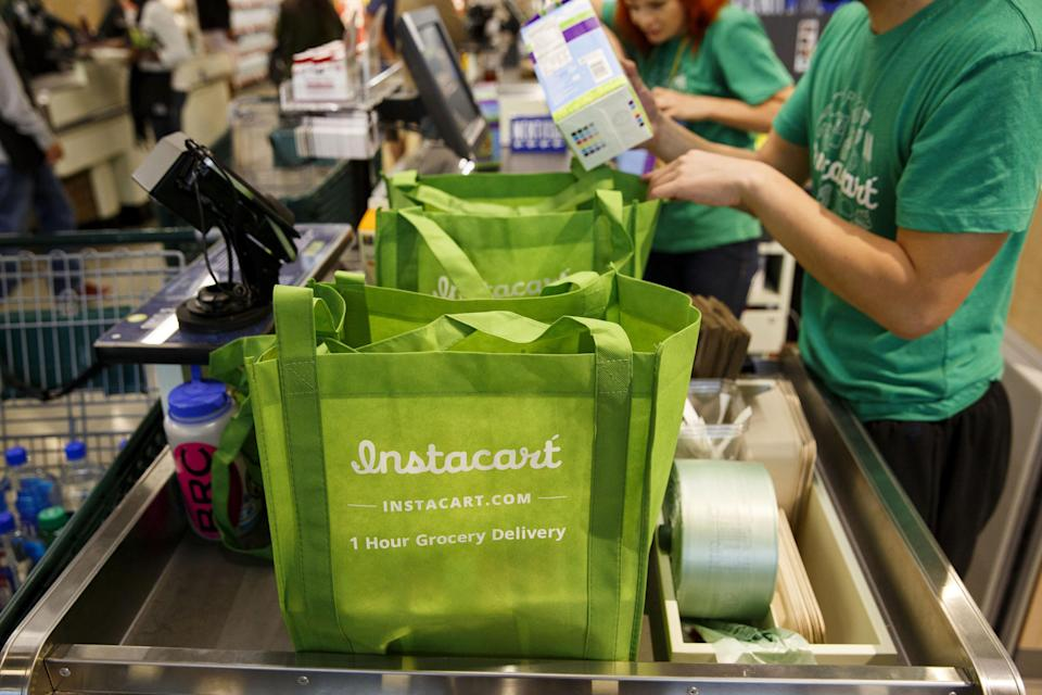 InstaCart employees fulfill orders for delivery at the new Whole Foods Market Inc. store in downtown Los Angeles, California, U.S., on Monday, Nov. 9, 2015. Located beneath the recently opened Eighth & Grand residences, the 41,000-square-foot store features a juice bar, fresh poke, expanded vegan options in all departments, a coffee bar (with cold brew on tap), more than 1,000 hand-picked wines, home delivery via Instacart and bar-restaurant The Eight Bar. Photographer: Patrick T. Fallon/Bloomberg via Getty Images