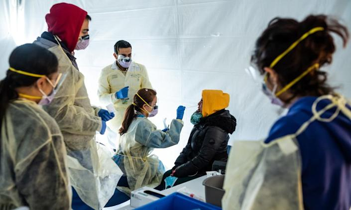 """<span class=""""element-image__caption"""">Doctors test hospital staff for coronavirus outside the emergency department at St Barnabas hospital in New York City. The US has conducted 1.3m tests so far.</span> <span class=""""element-image__credit"""">Photograph: Misha Friedman/Getty Images</span>"""