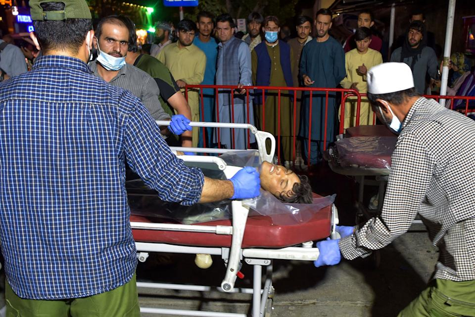 EDITORS NOTE: Graphic content / Volunteers and medical staff bring an injured man on a stretcher to a hospital for treatment after two powerful explosions, which killed at least six people, outside the airport in Kabul on August 26, 2021. / AFP / Wakil KOHSAR