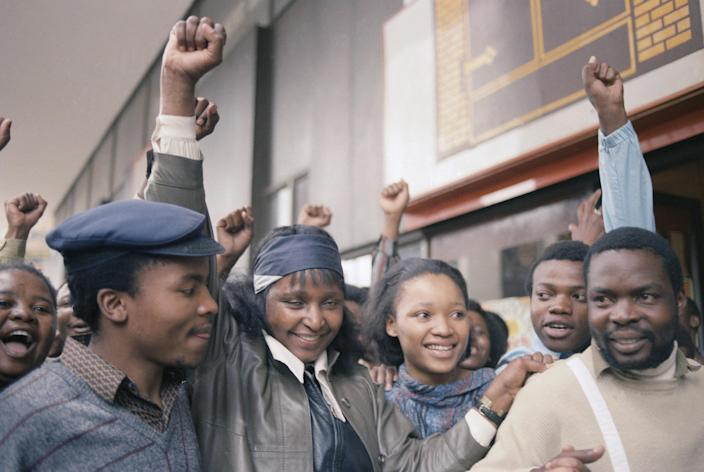 <p>Activist Winnie Mandela raises a clenched fist after appearing briefly in the Johannesburg Magistrate's Court on Jan. 22, 1986. Mrs. Mandela, who was held by police in Soweto on Sunday for defying her banning order, was released on her own recognizance and ordered to appear in the Krugersdorp Magistrate's Court, west of Johannesburg. (Photo: Greg English/AP) </p>