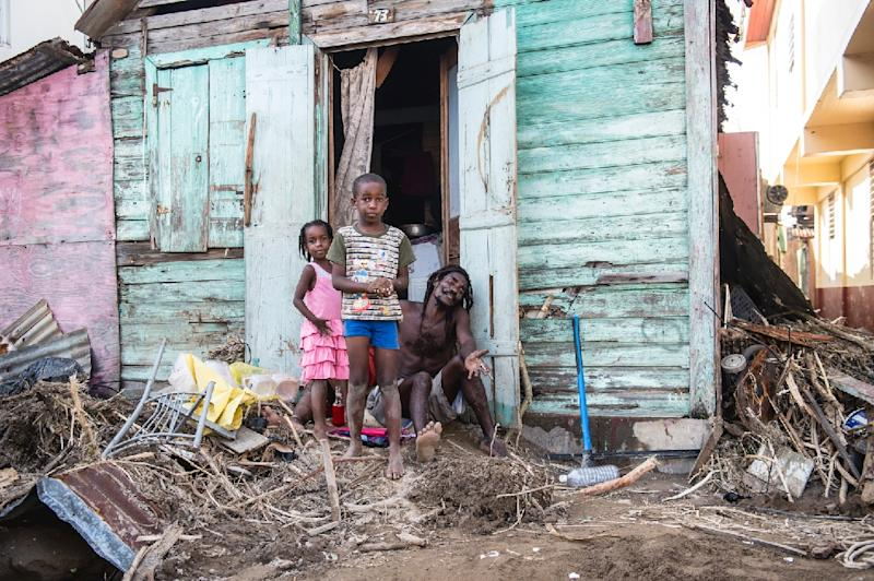A family stand outside their house in Roseau, on the Caribbean island of Dominica after Hurricane Maria hit the island (AFP Photo/Lionel CHAMOISEAU)