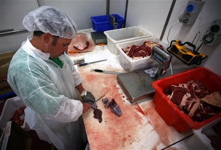 Butcher Trevor Hart cuts up kangaroo meat at a meat packing and distribution warehouse in western Sydney November 6, 2013. REUTERS/David Gray