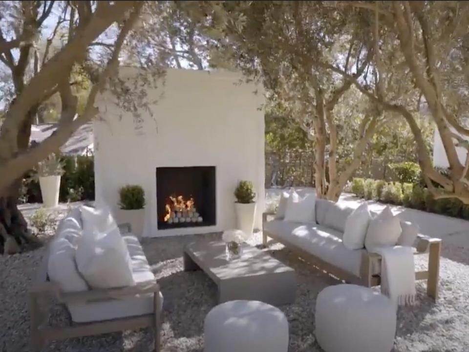 An outdoor fireplace with two couches, a coffee table, and two cushions surrounded by olive trees.